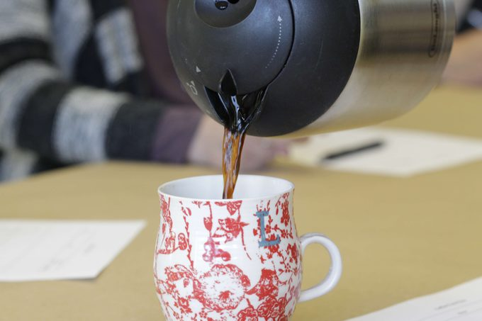 Coffee being poured into a red and white mug