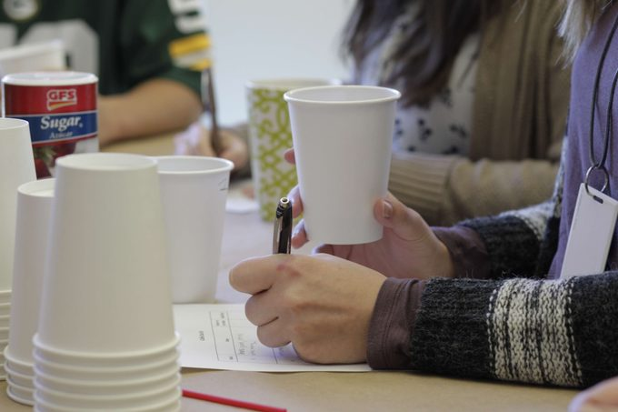 Person holding a cup of coffee as they take notes