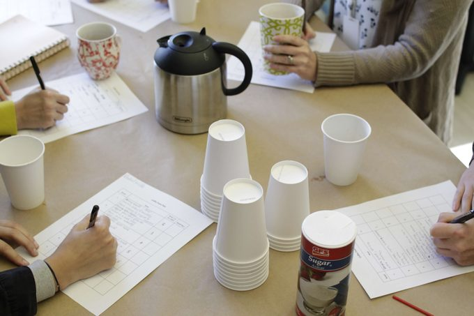 Taste testers taking notes surrounded by pots of coffee and cups