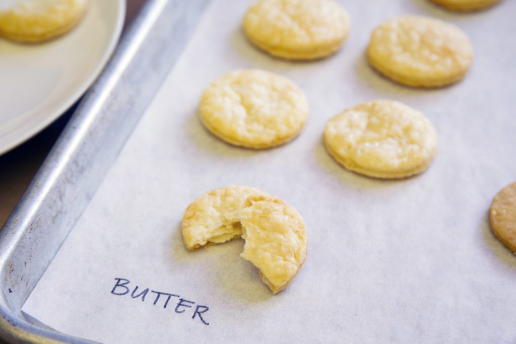 "Pie crust with butter taste test - cookie-shaped pieces shown on a baking sheet labeled with ""butter"""