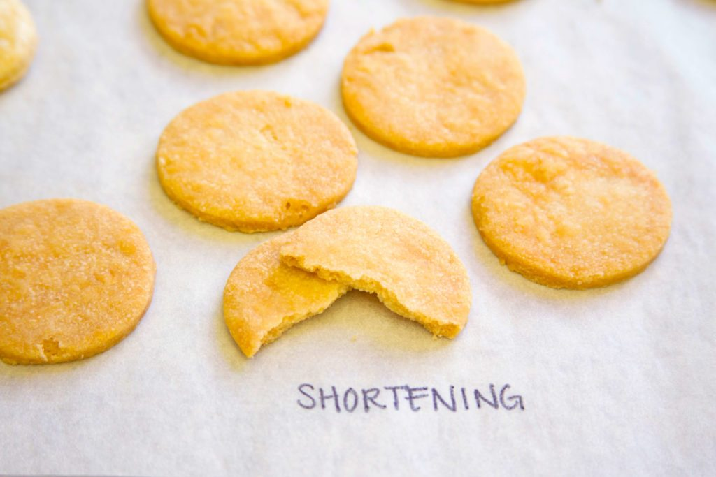 "Pie crust with shortening taste test - cookie-shaped pieces shown on a baking sheet labeled with ""shortening"""
