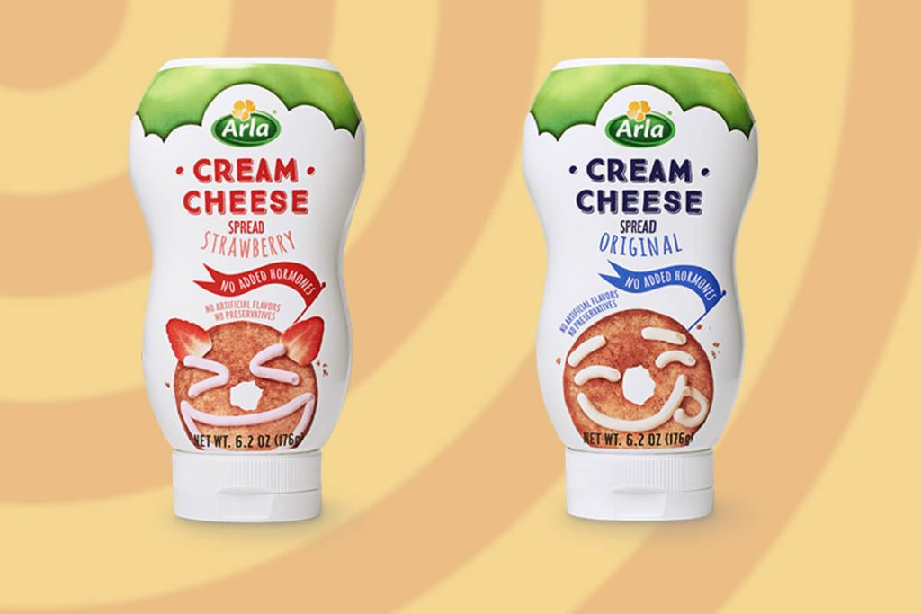 Two bottles of squeezable cream cheese against an orange and yellow background