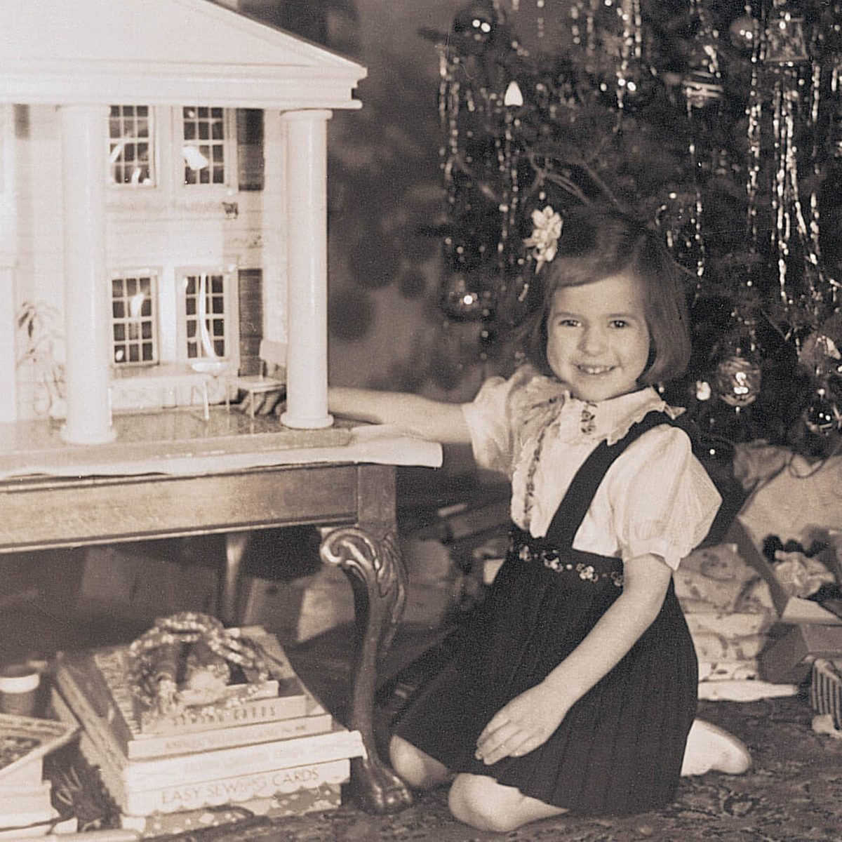 Black and white photo of a young girl beside a dollhouse