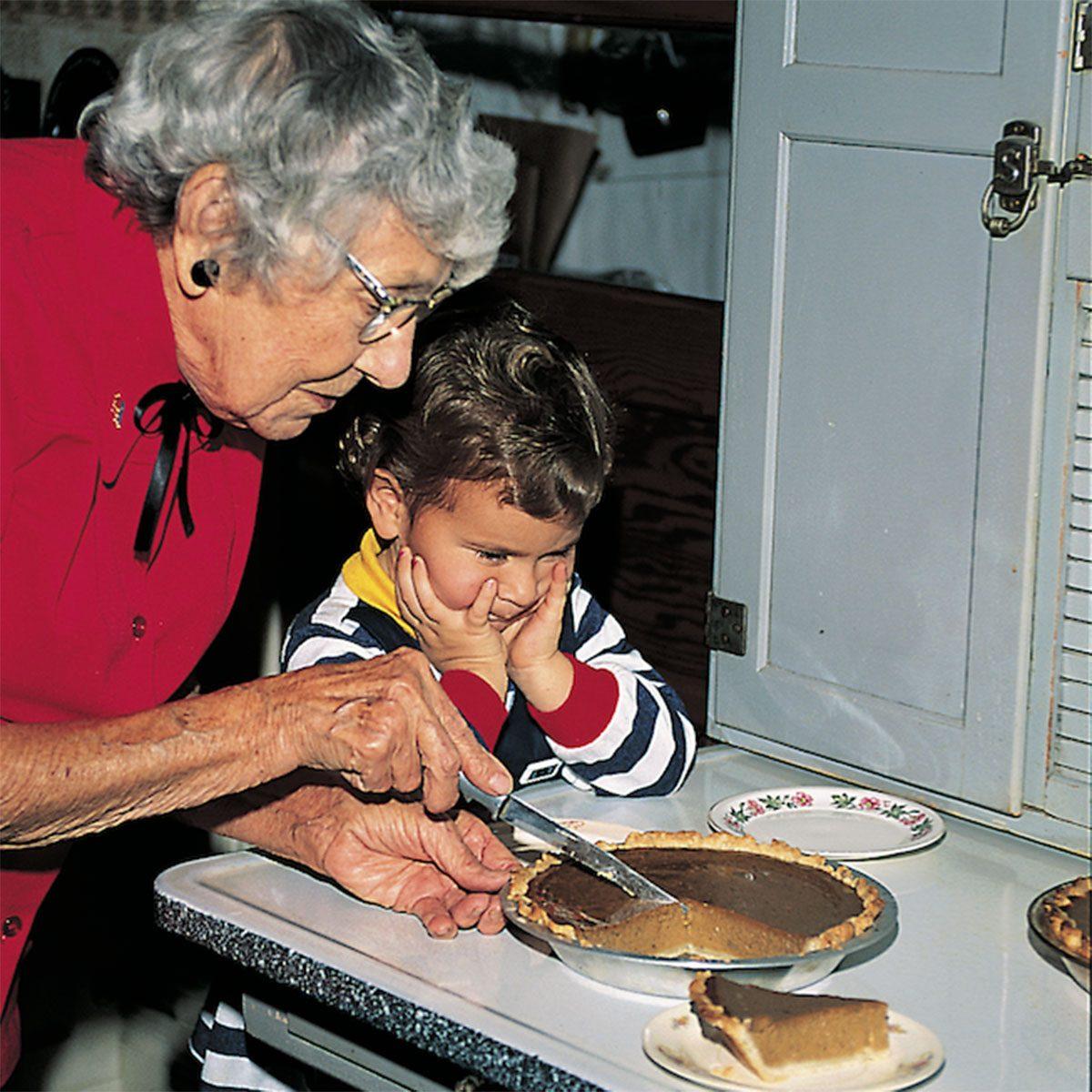 Grandma cutting a slice of pie for her grandchild
