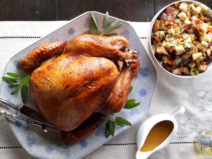 Roasted turkey on a nice platter beside a bowl of stuffing and gravy