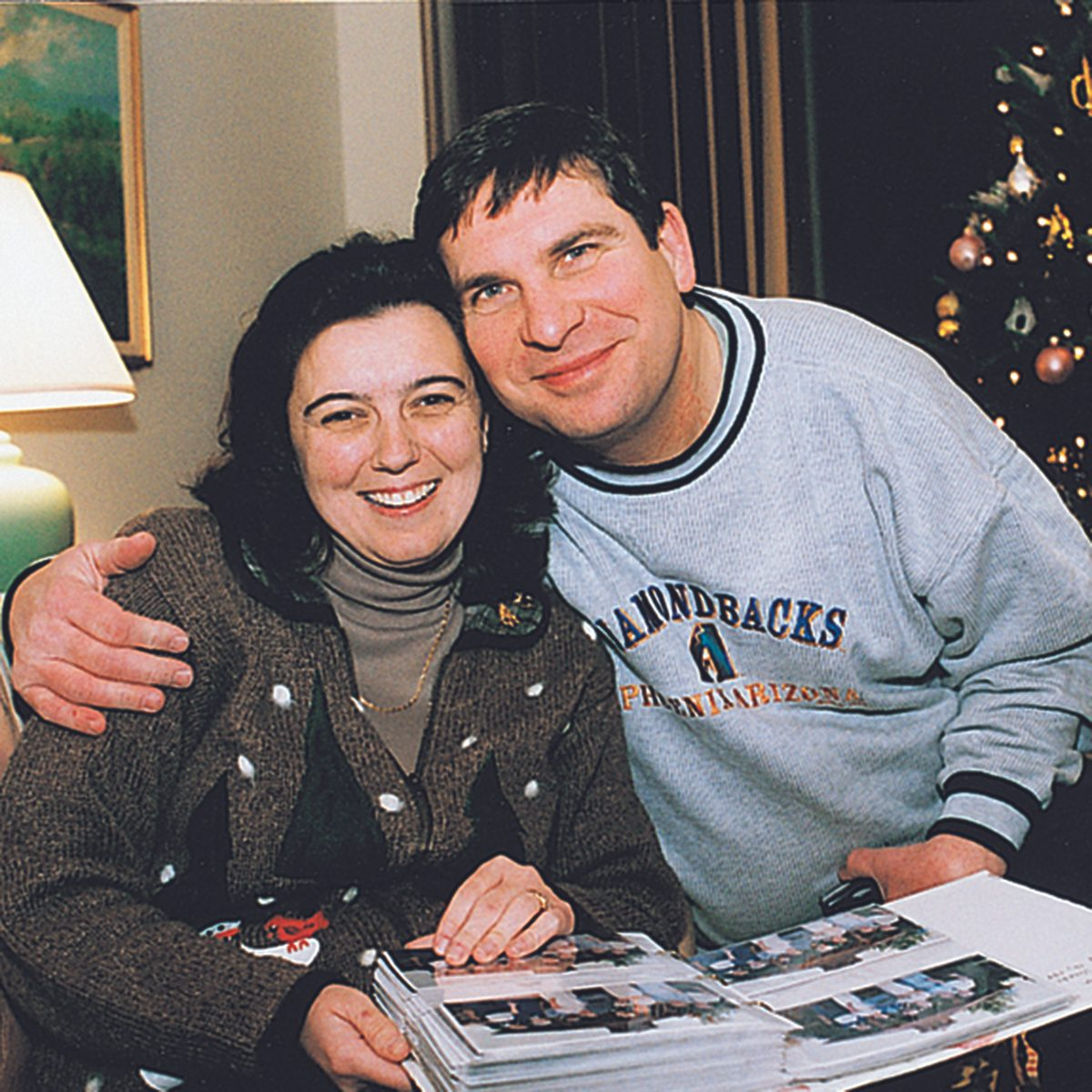 Man and woman hugging over a photo book of Christmas memories