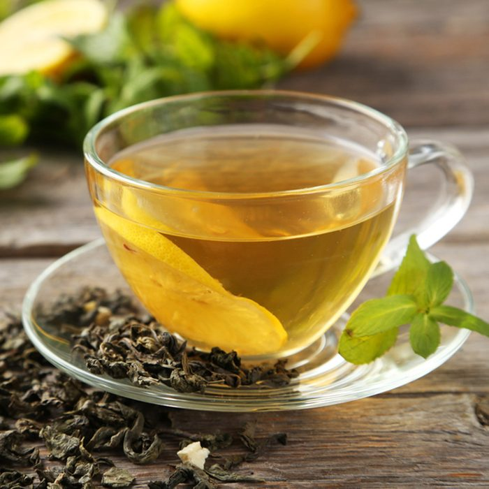 Cup with green tea on grey wooden background; Shutterstock ID 251566309