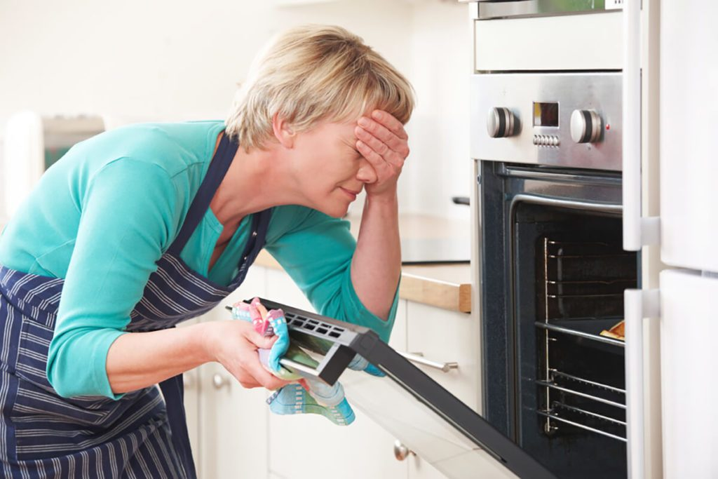 Woman Looking In Oven And Covering Eyes Over Disastrous Meal