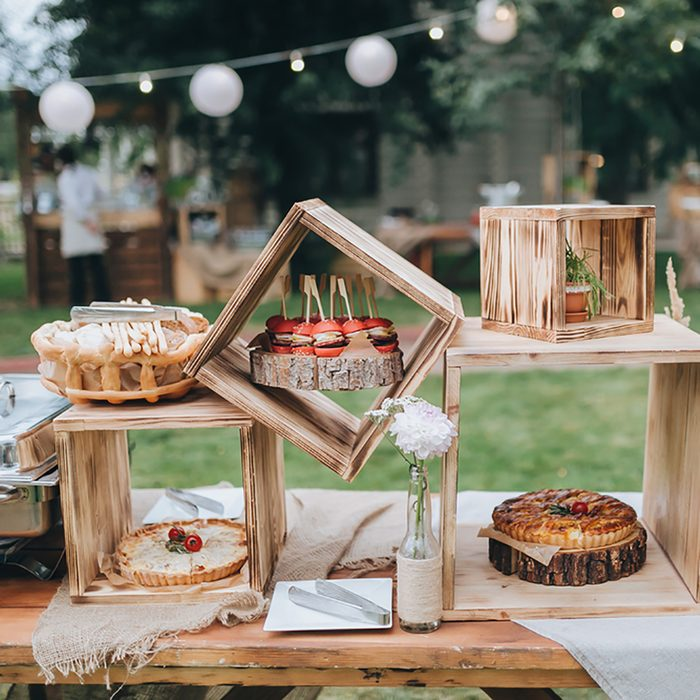 on decorated buffet table in wooden boxes are cakes and snacks; Shutterstock ID 314779967