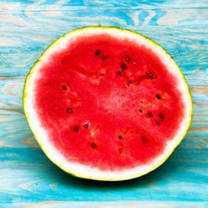 Half of watermelon on blue wooden background