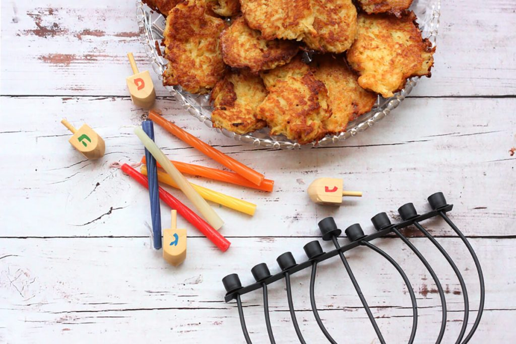 Latkes meal with items of Jewish Chanukkah holiday on a wooden background