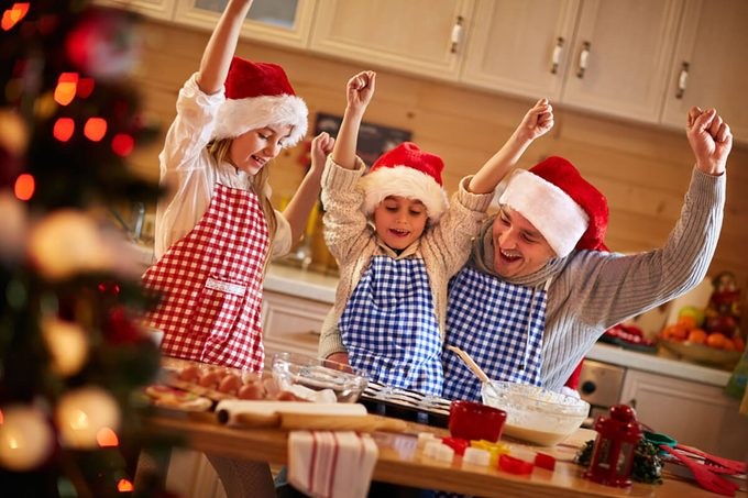 Happy father and children enjoying preparing Christmas cookies