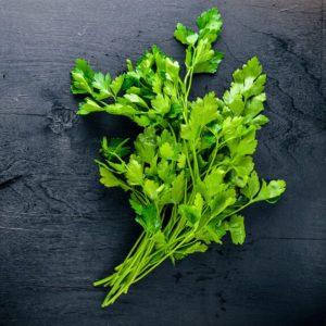 Fresh parsley on black wooden background
