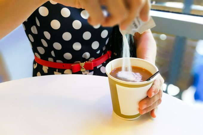 Hand pouring unhealthy non dairy creamer from sachet into hot coffee
