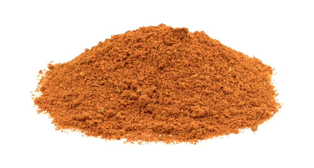 A small pile of taco seasoning isolated on a white background.