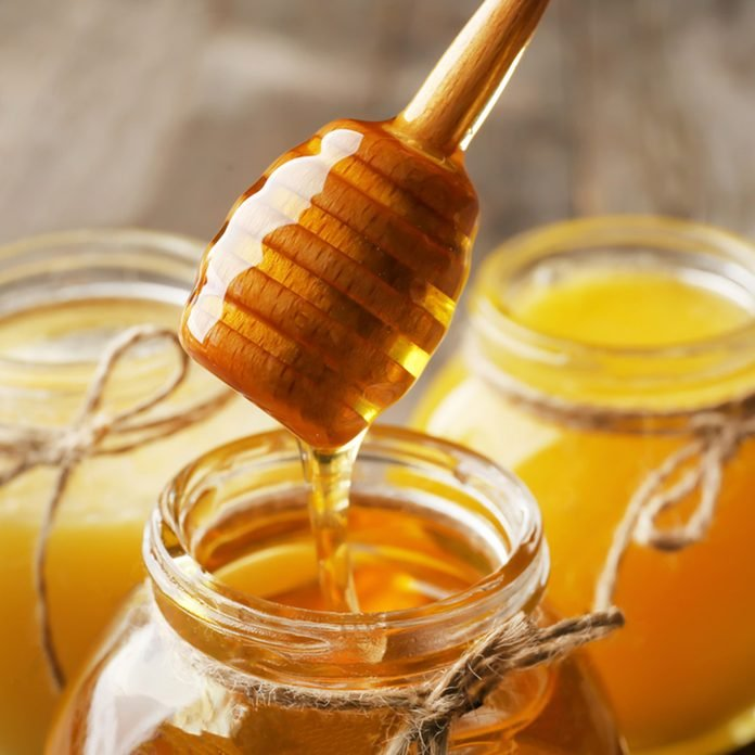Pouring aromatic honey into jar, closeup; Shutterstock ID 764193367