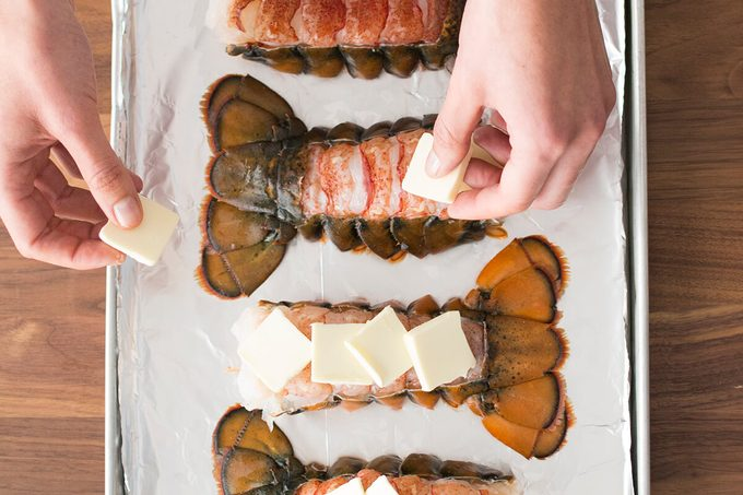 Person putting squares of butter on the opened lobster tails