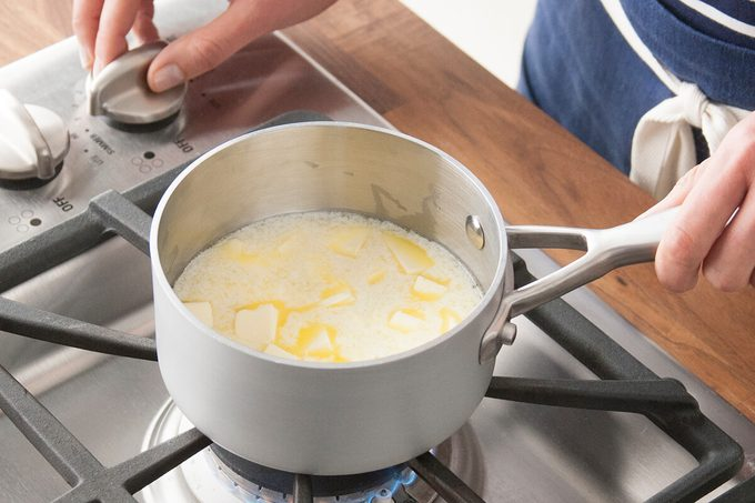 Person melting butter in a pot on the stove