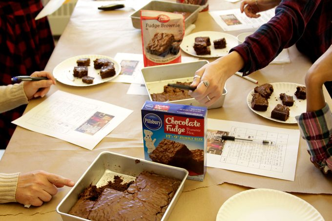 Plates of brownies beside papers and pens as the taste testers dig in