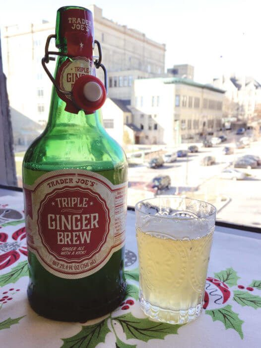 Ginger brew bottle and cup in front of a window