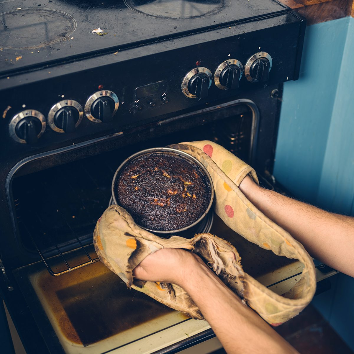 The hands of a man is removing a burnt cake from the oven