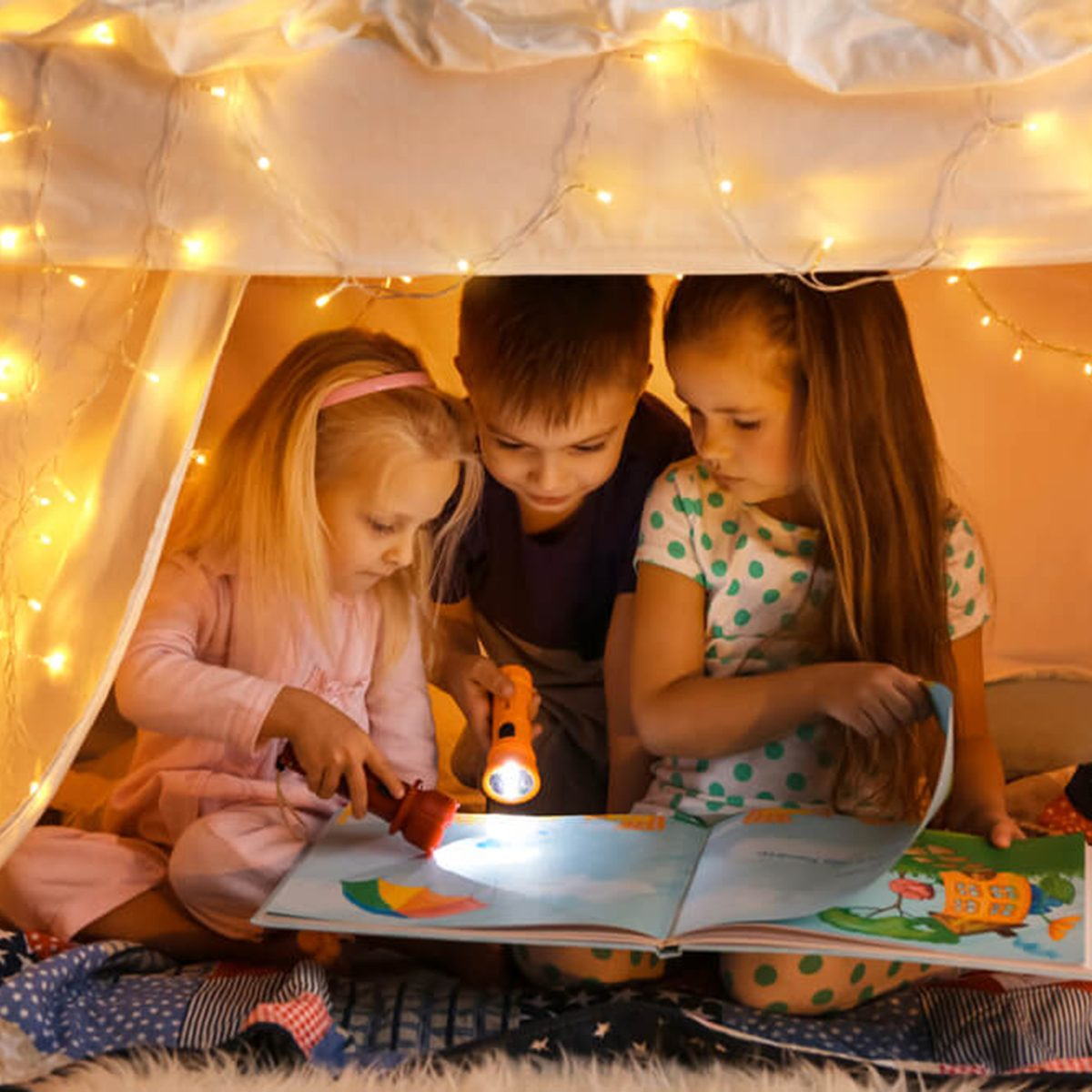 Children reading a story together under lit canopy
