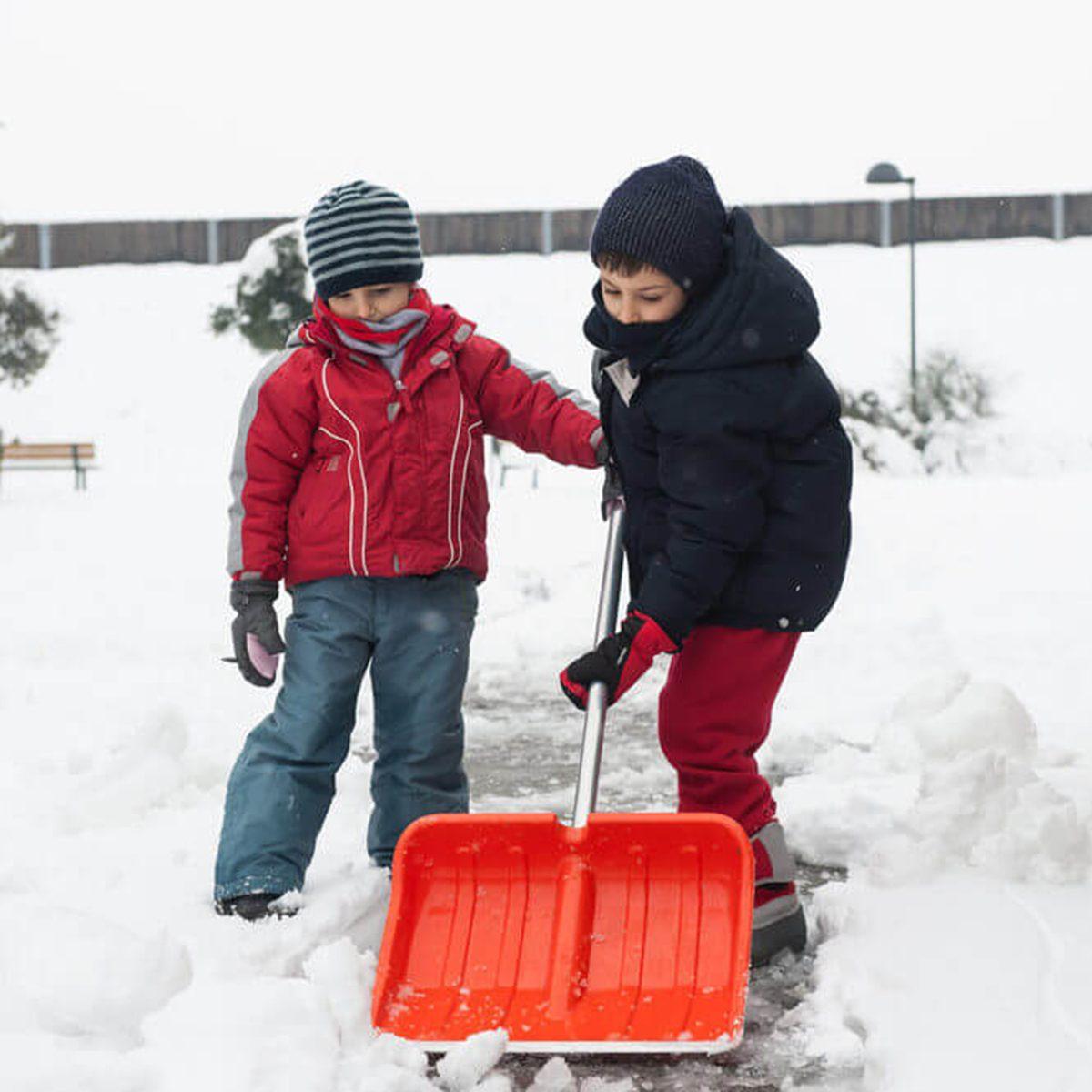 Two children shoveling snow