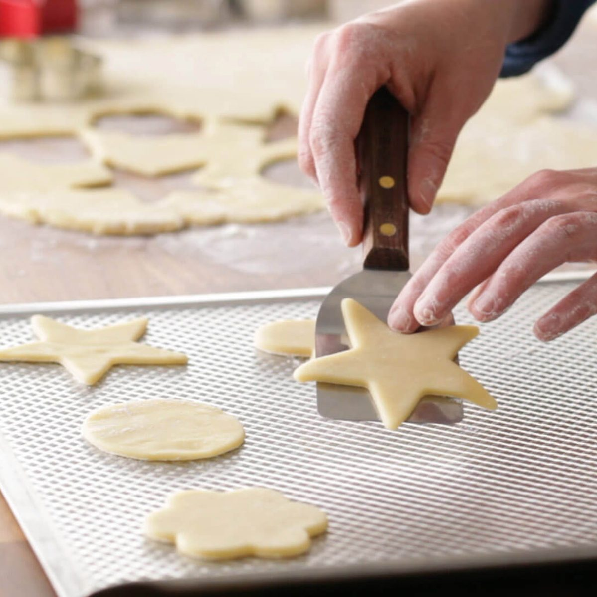 Person using a spatula to pick up sugar cookies