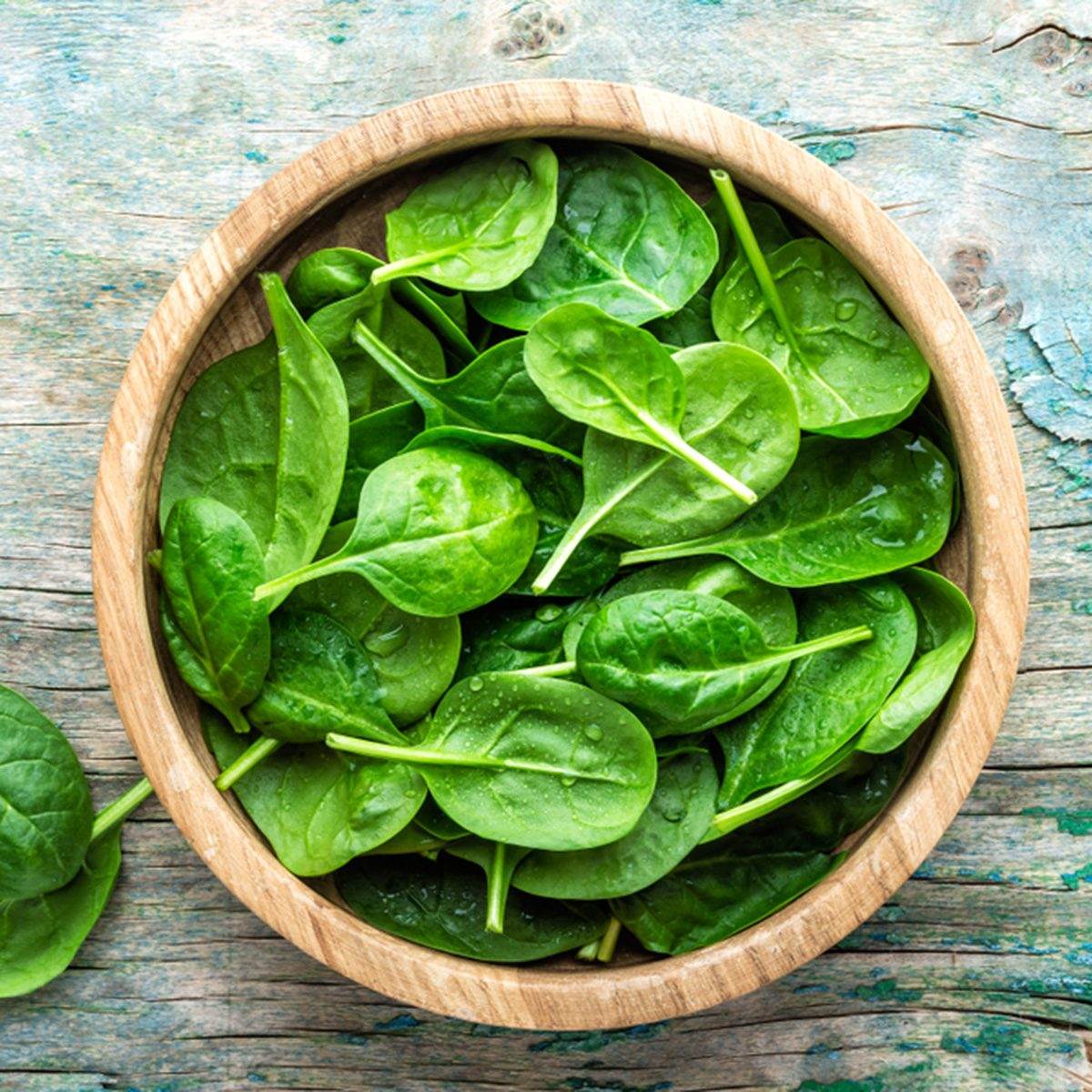 Fresh baby spinach leaves in bowl on wooden background; Shutterstock ID 1022814211; Job (TFH, TOH, RD, BNB, CWM, CM): Taste of Home
