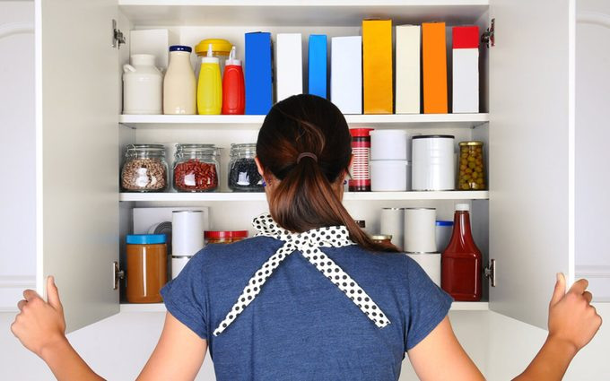 A woman seen from behind opening the doors to a fully stocked pantry. The cupboard is filled with various food stuff and groceries all with blank labels. Horizontal format the woman is unrecognizable
