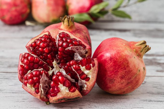Half pomegranate and raw pomegranates on a white wooden background