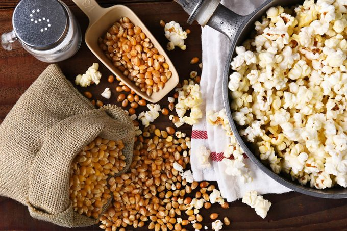 Top view of a pot full of freshly popped popcorn with salt and unpopped kernels on the side.