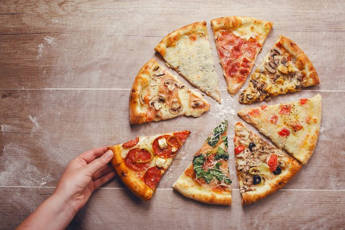 slices of pizza with different toppings on a wooden background
