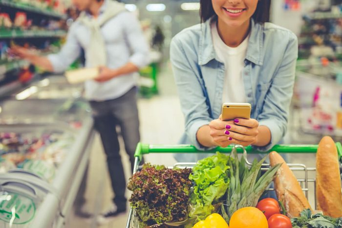 Cropped image of girl leaning on shopping cart, using a mobile phone and smiling, in the background her boyfriend is choosing food