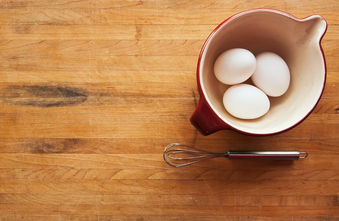 A view looking down on a red ceramic bowl filled with eggs on a butcher block counter with a whisk sitting to the side