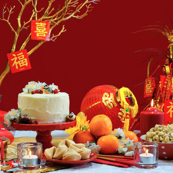 Chinese New Year party table in red and gold theme with food and traditional decorations.; Shutterstock ID 560002339