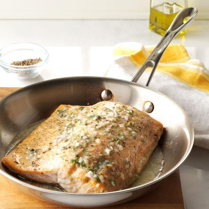 Oven-roasted salmon cooked in a hot skillet.