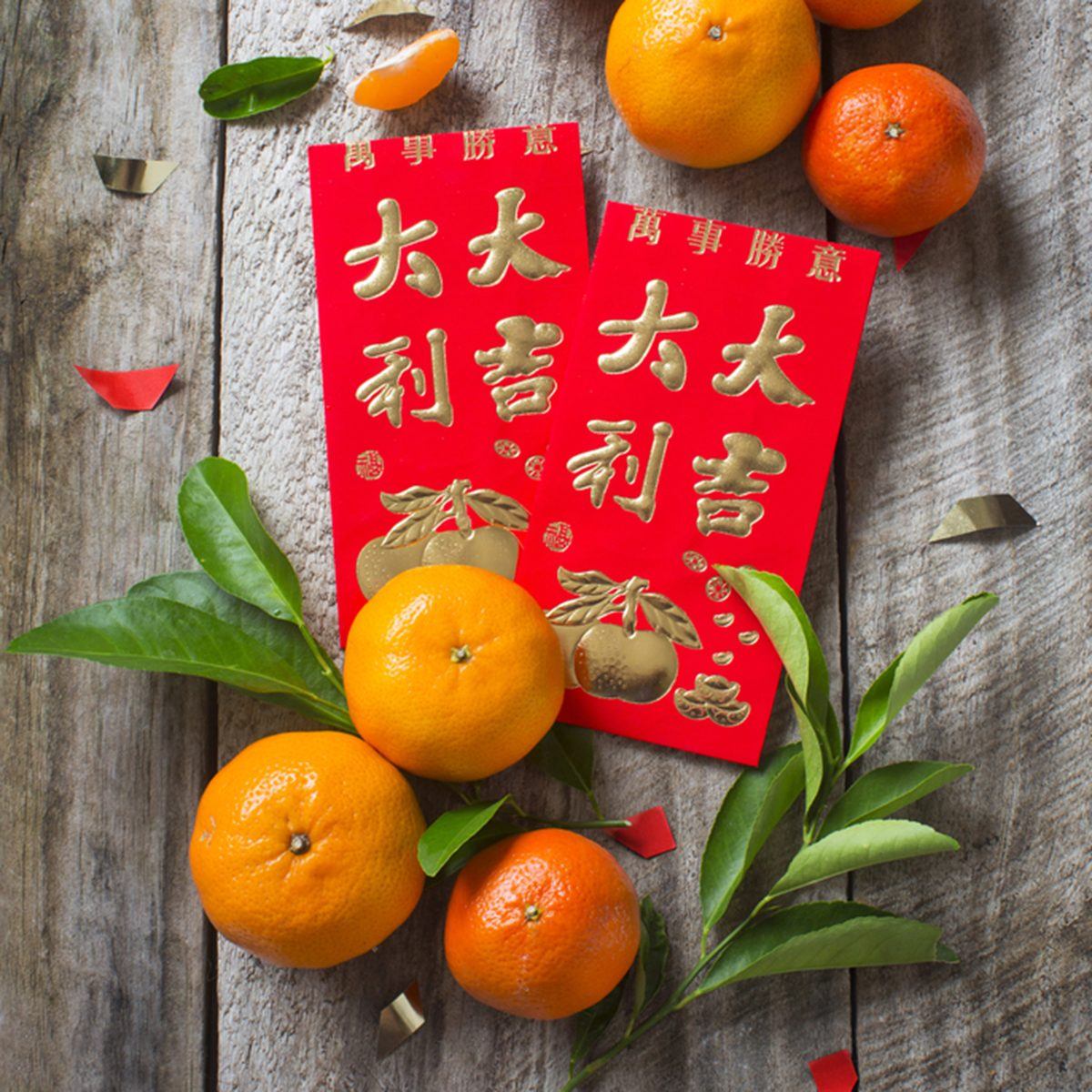 "Mandarin oranges and Chinese new year red packet with text ""Good luck and Great fortune"" and smaller text ""All the Best"" printed placed on rustic wooden background.; Shutterstock ID 361980683"