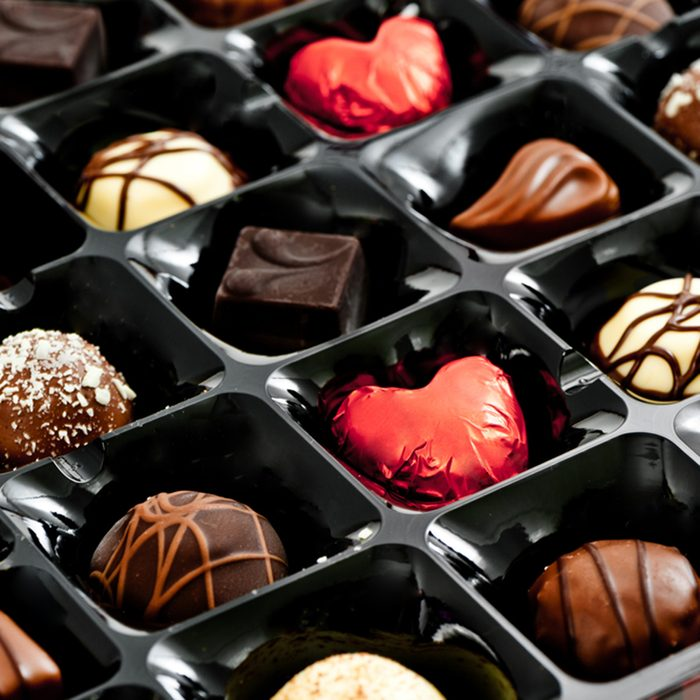 chocolates in a box, with red love heart shaped chocolate; Shutterstock ID 123648574