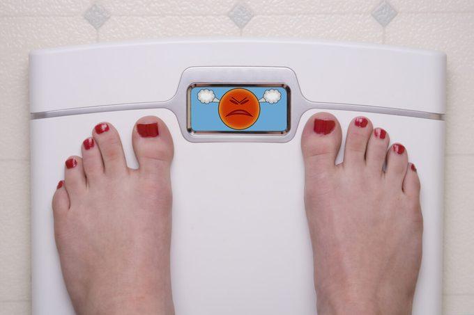 Digital Bathroom Scale Displaying an Angry Emoji