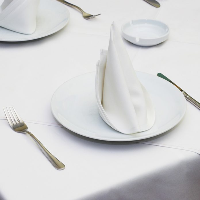 Empty served restaurant table with white tablecloth; Shutterstock ID 2382298