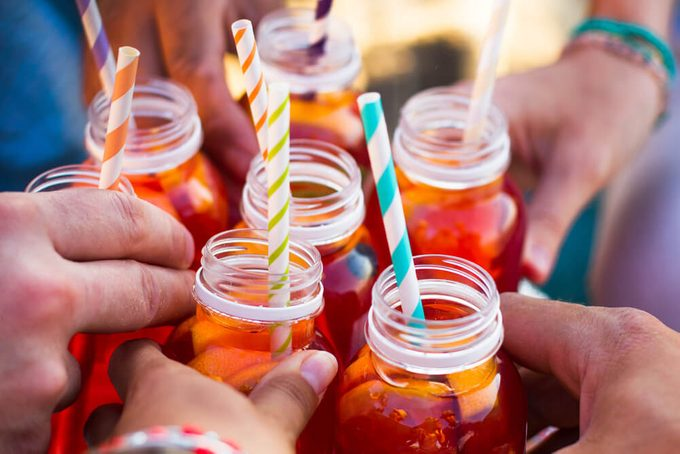 Picnic theme: group of friends holding drinks, toast , close-up