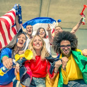 Group of sport supporters at stadium - Fans of diverse nations screaming to support their teams - Multi-ethnic people having fun and celebrating on tribune at a sport event