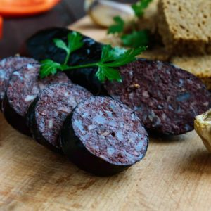 Morcillo (Spanish black pudding, blood sausage), cutting slices, black rye bread in a heart shape, pepper, garlic on a wooden board.