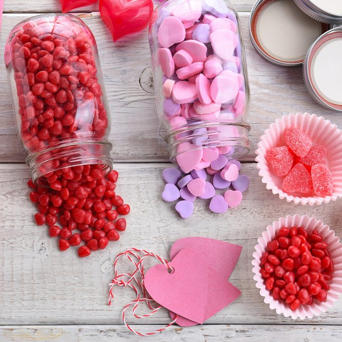 High angle view of different Valentines Day Candies on a rustic white wood table. Canning jars on their sides with candy spilling out.; Shutterstock ID 549418111