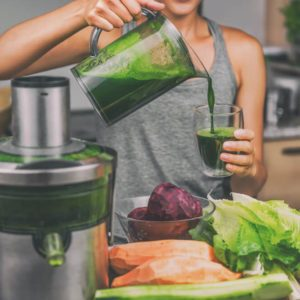 Woman juicing making green juice with juice machine in home kitchen. Healthy detox vegan diet with vegetable cold pressed extractor to extract nutrients for smoothie drink