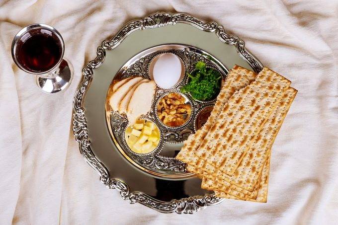 A Passover Seder plate, glass of wine and matzo for a Passover seder.