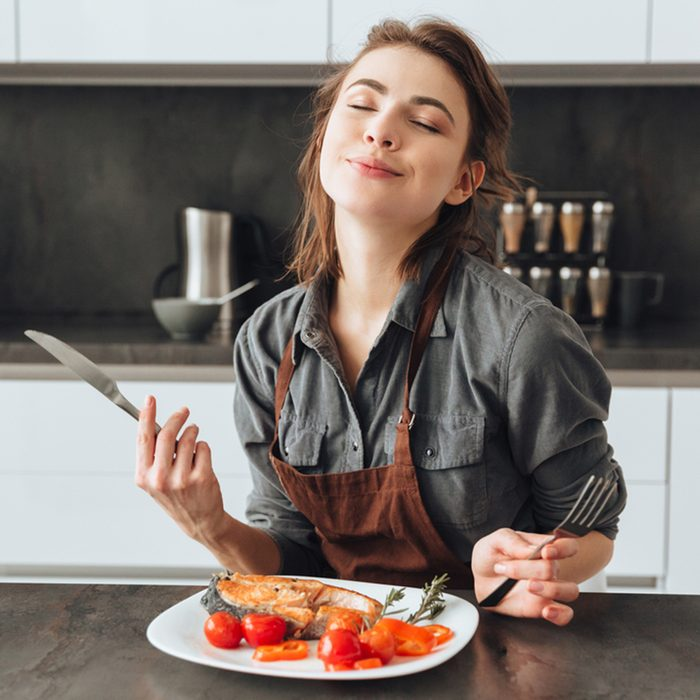 Image of pretty young woman sitting in kitchen while eating fish and tomatoes.; Shutterstock ID 579904396