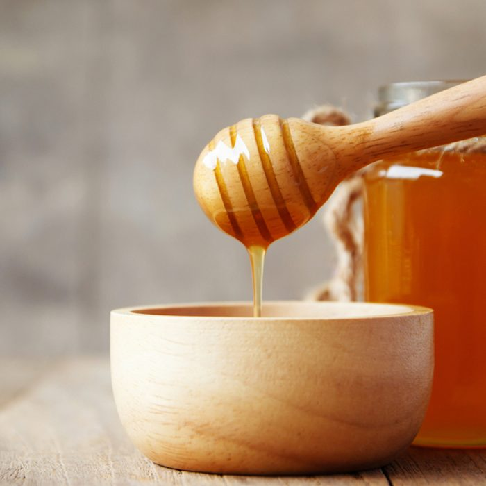 Honey being poured into wooden bowl