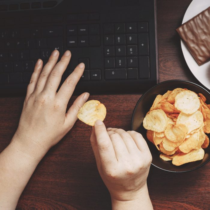Unhealthy snack at workplace. Hands of woman working at computer and taking chips from the bowl. Bad habits, junk food, high calorie eating, weight gain and lifestyle concept; Shutterstock ID 1117577912; Job (TFH, TOH, RD, BNB, CWM, CM): TOH
